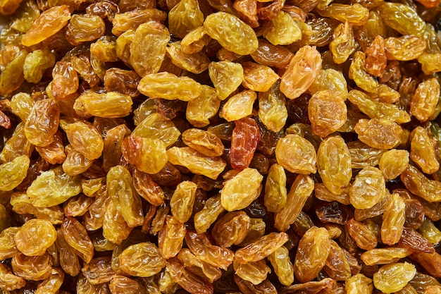 Raisins lie on the table and form a food background.