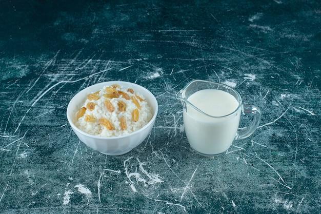 Изюм на миске рисового пудинга рядом со стаканом молока на синем фоне. фото высокого качества