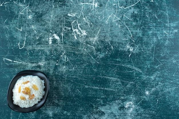 Изюм на миске рисового пудинга, на синем фоне. фото высокого качества
