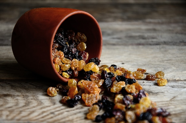 Raisins scattered on wooden planks of wooden utensils.