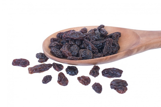Raisins (sultanas) in spoon wood isolated on white