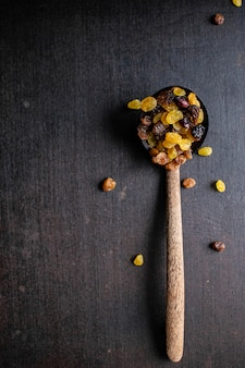Raisins and sultanas on a wooden spoon