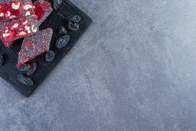 Raisins and turkish delights in a cutting, on the marble background.