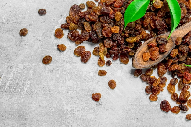Raisins with green leaves on rustic table.