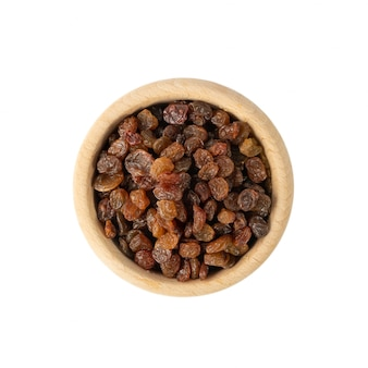 Raisins in wood bowl isolated