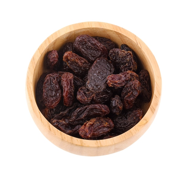 Raisins in wooden bowl isolated