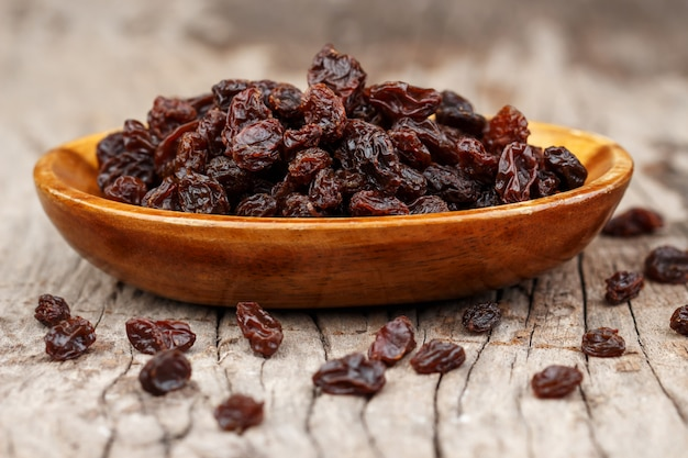 Raisins in a wooden bowl on the old wooden table