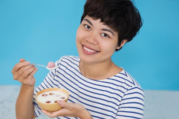 Счастливый молодых азиатских женщин, едят помидор raita