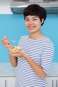 Улыбающиеся молодые азиатские женщины едят помидор raita
