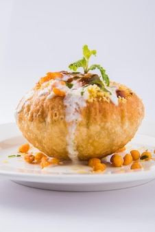 Rajasthani shahi raj kachori, stuffed with potato and sprout filling. served with curd, chutney and sev in a plate, isolated over colourful or wooden background. selective focus