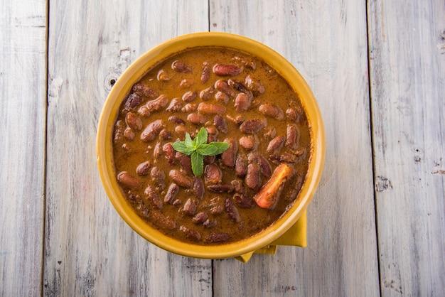 Rajma or razma는 향신료와 함께 걸쭉한 육즙에 익힌 붉은 강낭콩으로 구성된 인기 있는 북부 인도 음식입니다. 제라 라이스 & 그린 샐러드와 함께 그릇에 제공