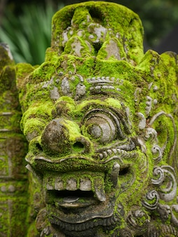 Rakasa balinese stone sculpture covered with moss.