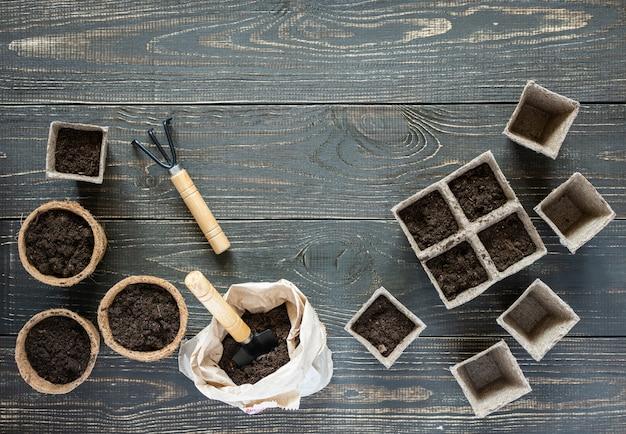 Грабли и экологически чистые горшки для рассады на деревянном фоне, небольшая сумка с землей и садовой лопаткой и граблями