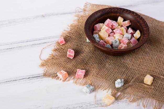 白い木製のテーブルの上のジュート布の上にボウルに多色rakhat-lukum