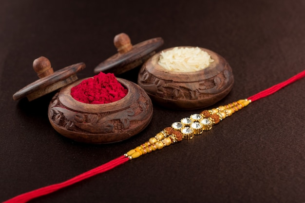 Raksha bandhan composition with an elegant rakhi, rice grains and kumkum. a traditional indian wrist band which is a symbol of love between brothers and sisters.