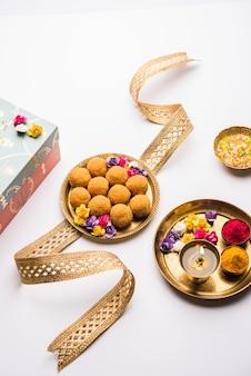 Raksha bandhan festival : conceptual rakhi made using plate full of bundi laddu sweet with band and pooja thali. a traditional indian wrist band - symbol of love between brother and sister Premium Photo