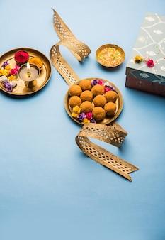 Raksha bandhan festival : conceptual rakhi made using plate full of bundi laddu sweet with band and pooja thali. a traditional indian wrist band - symbol of love between brother and sister