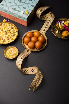 Raksha bandhan festival : conceptual rakhi made using plate full of gulab jamun sweet with band and pooja thali.