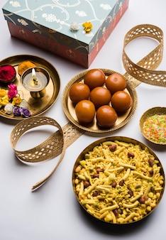 Фестиваль ракша-бандхана: концептуальный ракхи, сделанный с использованием тарелки, полной сладостей гулаб джамун, с группой и пуджа тали.