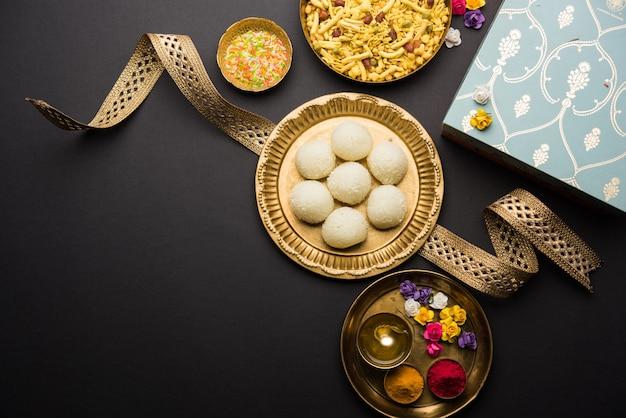 Фестиваль ракша-бандхана: концептуальный ракхи, сделанный с использованием тарелки, полной сладостей расгулла с оркестром. традиционный индийский браслет - символ любви между братьями и сестрами.