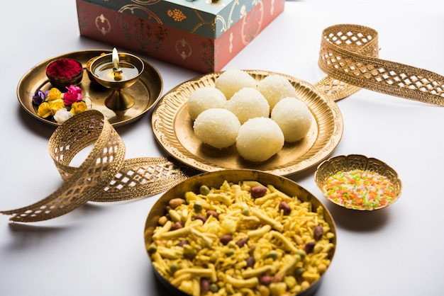 Raksha bandhan festival : conceptual rakhi made using plate full of rasgulla sweet with band. a traditional indian wrist band which is a symbol of love between brothers and sisters