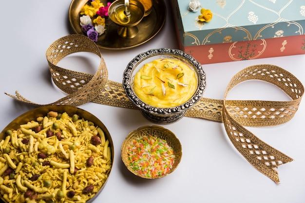 Фестиваль ракша-бандхана: концептуальный ракхи, сделанный с использованием шрикханда в чаше с оркестром и пуджа тали. традиционный индийский браслет - символ любви между братьями и сестрами.