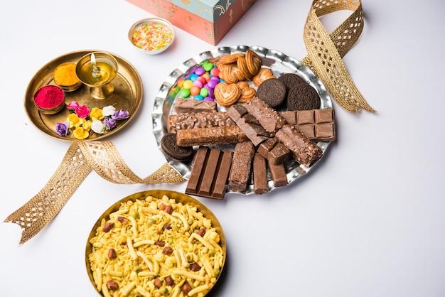 Приветствие фестиваля ракша-бандхан: концептуальный ракхи, сделанный с использованием тарелки, полной шоколадных конфет и печенья, с модной лентой и пуджей тали. выборочный фокус