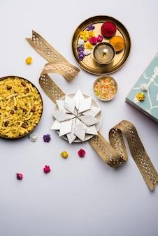Приветствие фестиваля ракша-бандхана: концептуальный ракхи, сделанный с использованием тарелки, полной каджу катли барфи или бурфи, и причудливой группы и пуджи тали. выборочный фокус