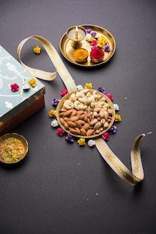 Raksha bandhan festival greetings: conceptual rakhi made using a plate full dry fruits like cashew, pistachio, almond with fancy band and pooja thali. selective focus