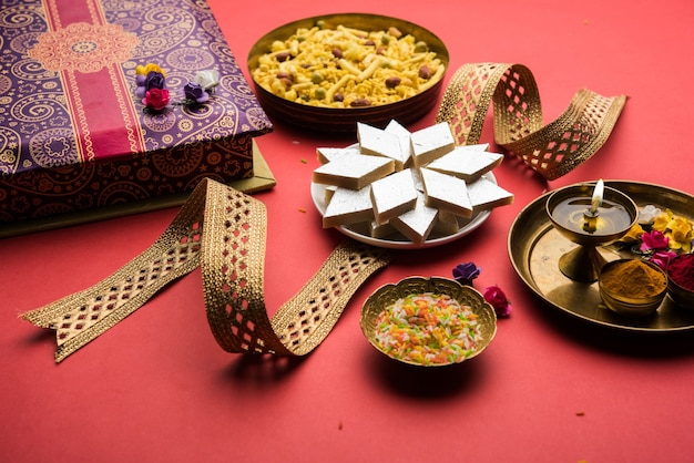 Raksha bandhan festival greetings: conceptual rakhi made using a plate full of kaju katli barfi or burfi and fancy band and pooja thali. selective focus