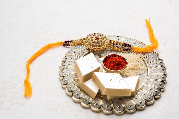 Raksha bandhan greeting  rakhi and gift with sweet kaju katli or mithai and rice grains kumkum
