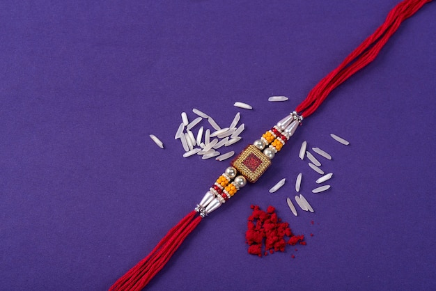 Raksha bandhan : rakhi with rice grains and kumkum. traditional indian wrist band which is a symbol of love between brothers and sisters.