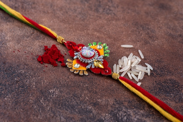 Raksha bandhan : rakhi with rice grains and kumkum, traditional indian wrist band which is a symbol of love between brothers and sisters.