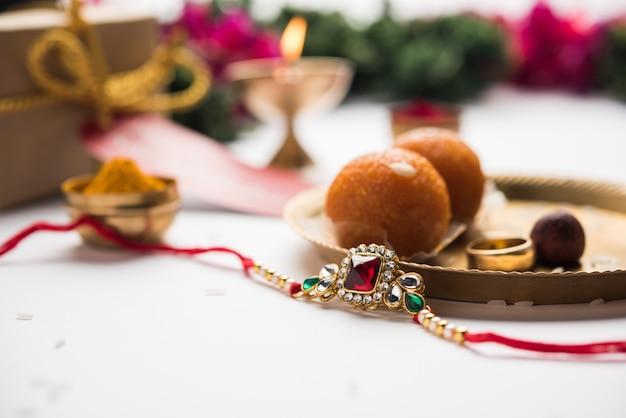 Raksha bandhan / rakshabandhan rakhi with haldi kumkum rice, sweet mithai, gift box, selective focus