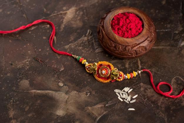 우아한 rakhi, rice grains 및 kumkum을 가진 raksha bandhan. 형제 자매 사랑의 상징 인 인도 전통 손목 밴드.