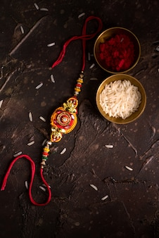 Raksha bandhan with an elegant rakhi, rice grains and kumkum. a traditional indian wrist band which is a symbol of love between brothers and sisters.
