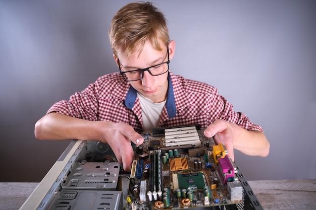 壊れたコンピューター、ビデオカード、メモリram、クーラー、プロセッサ、ハードドライブを修復する男