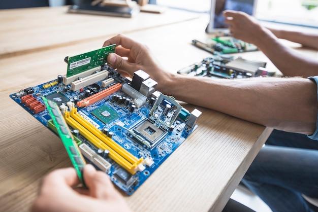 技術者は、コンピュータのマザーボードのソケットにramを置く