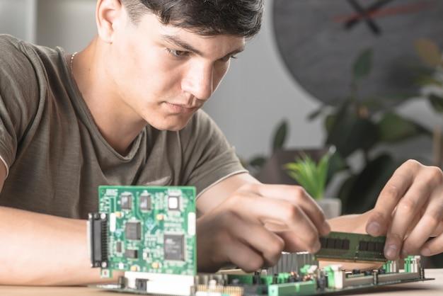 コンピュータマザーボードにramを挿入する技術者の学生