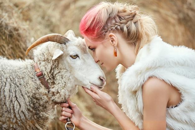 女性の顔に真っ赤な化粧は、角のあるramを抱擁します。女性の顔、髪の色の創造的なホットピンクメイク。羊を持つ女性の肖像画。秋の森を歩く