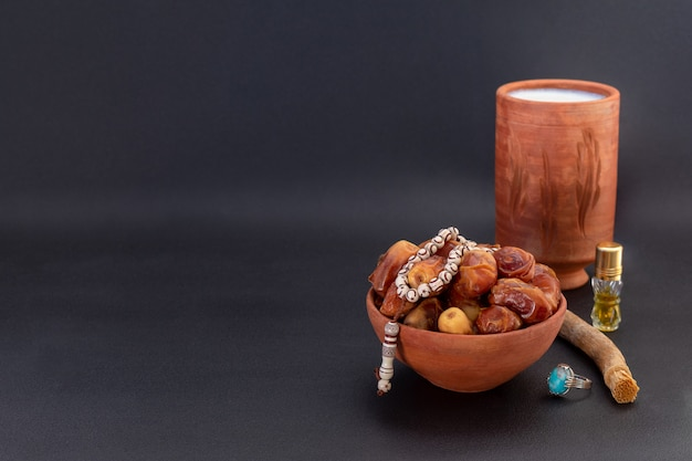 Ramadan composition with dates, miswak, prayer beads, itar and milk in ceramic containers