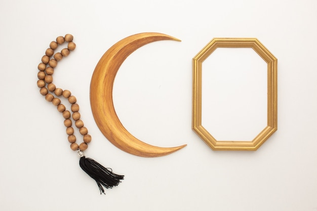Концепция рамадана. золотой месяц, четки и рамка для вашего текста. фото высокого качества