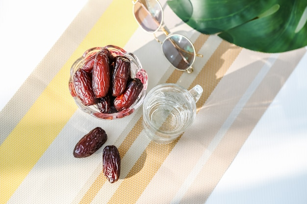 Ramadan concept and some date palms with a glass of water on a warm color palette table display