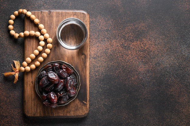 Ramadan dates in bowl glass of water wooden prayer beads on brown eid mubarak religious tradition