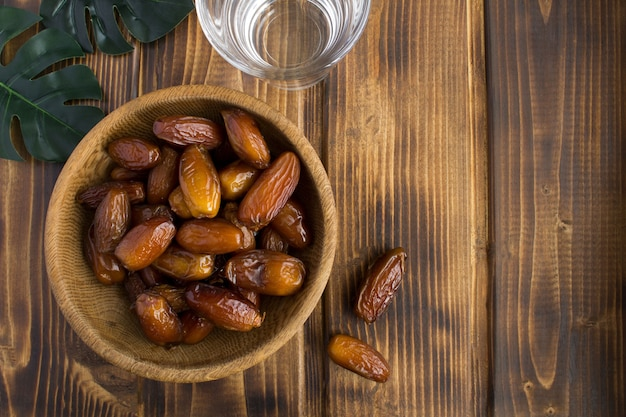 Ramadan dates in the brown bowl and water in the glass on the wooden background.top view.copy space.