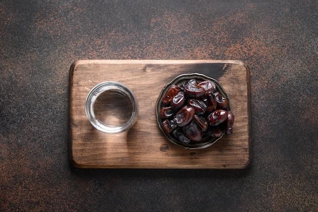 Рамадан финики в чаше и вода по религиозной традиции коричневый ид мубарак