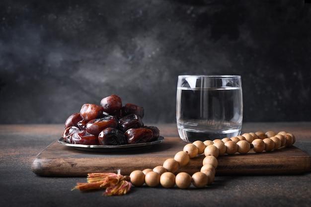 Рамадан финики в миске стакан воды деревянные четки на коричневой религиозной традиции ид мубарак