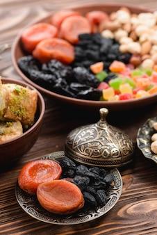 나무 질감 배경에 금속 접시에 라마단 건조 원시 유기농 말린 과일