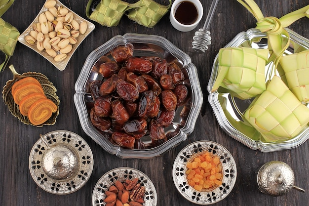 나무 테이블에 복사 공간이 있는 라마단 음식과 음료 개념. 날짜 과일, 견과류, 씨앗, 커피, 차, honeyand ketupat. ied al fitr를 위한 아라비아 이슬람식 음식