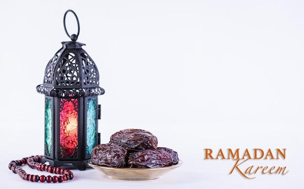 ラマダンの食べ物や飲み物のコンセプトラマダンアラビアンランプウッドロザリオと日付の果物
